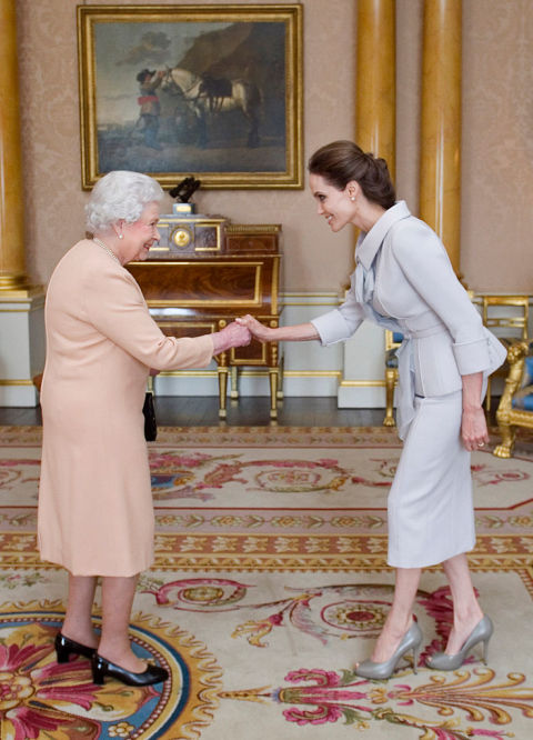 If you're a citizen of the United States, you can simply shake hands, but in Great Britain, men and women must bow or curtsy. When Angelina Jolie, who is a US citizen met the Queen, you see she did a little of all three...
