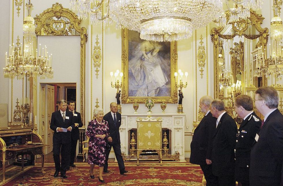 As soon as the Queen enters the room, everyone must stand to greet her and should not sit down until she does. Only then is it polite to take a rest.