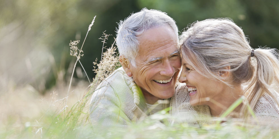 Happy elderly couple sitting in long grass